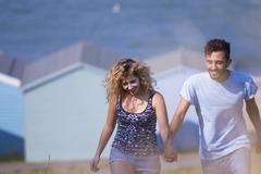 Young couple holding hands with beach huts in background - stock photo