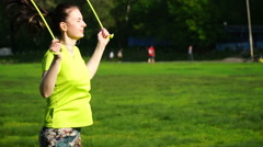 Footage woman jumping on a skipping rope in a park close-up Stock Footage