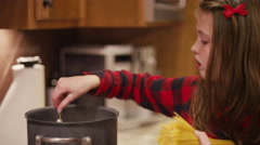Girl puts a spaghetti noodle into a pot of water and bites it Stock Footage