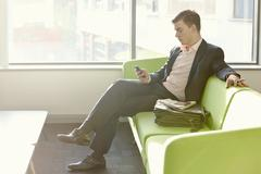 Businessman in departure lounge using cell phone Stock Photos