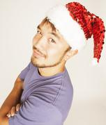 funy exotical asian Santa claus in new years red hat smiling - stock photo