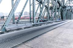 Empty pedestrian walkway near road on steel bridge Stock Photos