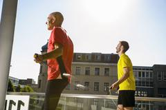 Two male athletes training with skipping ropes on city roof Stock Photos