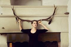 Portrait of young woman standing in front of antlers Stock Photos