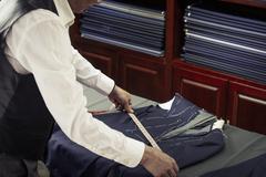 Tailor measuring garment in tailors shop - stock photo