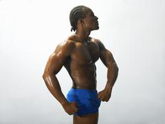Studio shot of male bodybuilder flexing abdominal muscles - stock photo