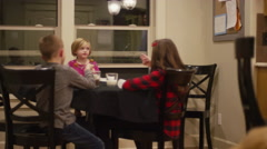 Three kids eating spaghetti and meatballs at the dinner table together Stock Footage