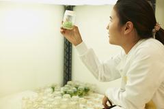 Female scientist examining plant sample in jar - stock photo