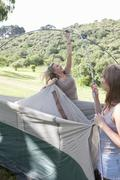 Two young females friends constructing tent - stock photo