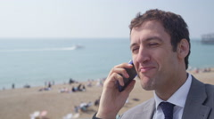 4k Portrait of smiling businessman talking on mobile phone at the beach Stock Footage