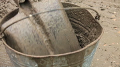 Builder Pouring Cement Into Bucket Stock Footage