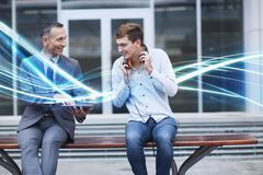 Businessman and young man watching digital tablet and waves of blue light Stock Photos