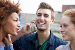 Three young adult friends, one talking on smartphone Stock Photos
