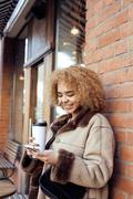 Young pretty african american women drinking coffee outside in cafe, modern Stock Photos