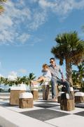 Father and son sitting on giant chess set, Providenciales, Turks and Caicos - stock photo