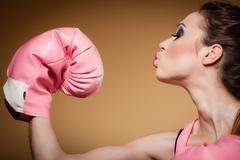 Female boxer wearing big fun pink gloves playing sports Stock Photos