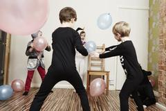 Children playing with balloons at birthday party Stock Photos