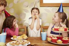 Children eating party food at birthday party Stock Photos