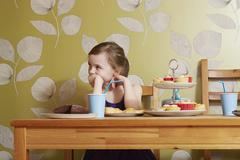Bored looking girl at table with party food Stock Photos