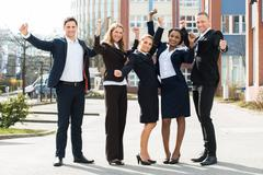 Group Of Happy Multi-racial Businesspeople Standing With Arm Raised In Front  Stock Photos
