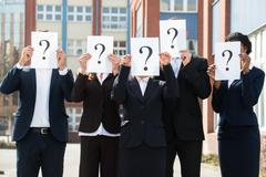 Group Of Businesspeople Hiding Face Behind Question Mark Sign;Outdoor - stock photo