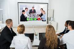 Group Of Businesspeople Together Videoconferencing At Workplace Kuvituskuvat