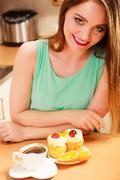 Woman with coffee and cake in kitchen. Gluttony. Stock Photos