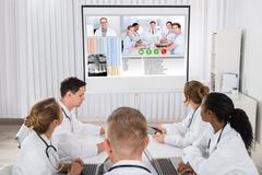 Group Of Doctors Videoconferencing With Male Doctor In Hospital Kuvituskuvat