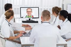 Group Of Doctors Videoconferencing With Male Doctor On Computer In Hospital Kuvituskuvat