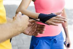 Personal trainer wrapping bandages around female boxers hand - stock photo