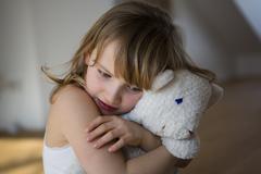 Distressed girl holding onto teddy bear Stock Photos