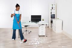 Young Female Janitor Sweeping Torn Paper Pieces On Hardwood Floor Stock Photos