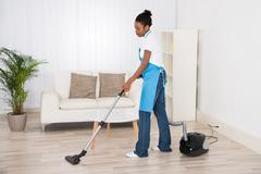 Young Female Janitor Cleaning Floor With Vacuum Cleaner In Room Kuvituskuvat