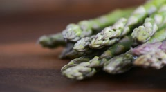 Macro close up of fresh asparagus spears on dark wood background, panning and Stock Footage
