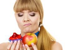 Woman choosing fruit or cake make dietary choice - stock photo
