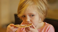 A little girl eating a pancake with her hands Stock Footage