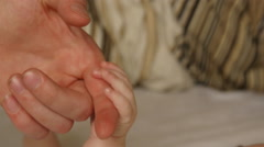 Baby adjusts grip on working mans hands Stock Footage