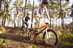 Twin brothers racing BMX bikes through muddy forest Kuvituskuvat