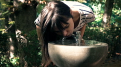 Young woman drinking water from dispenser in park, super slow motion 240fps Stock Footage