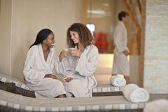 Two young women chatting on loungers in spa - stock photo