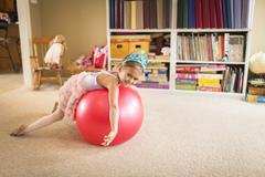 Portrait of cute young girl on top of exercise ball - stock photo
