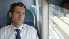 4K Tired businessman with earphones trying to get some sleep on train journey Stock Footage