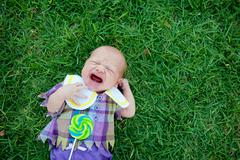 Baby lying on grass, crying Stock Photos