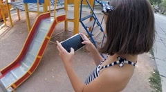 SLOW MOTION. Girl playing on a smartphone in the park Stock Footage