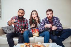 Amazed shocked friends watching tv and eating popcorn on sofa - stock photo