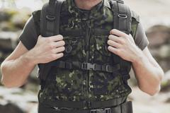 close up of young soldier with backpack in forest - stock photo