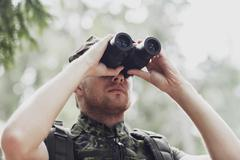 young soldier or hunter with binocular in forest - stock photo