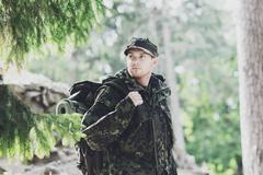 young soldier with backpack in forest - stock photo
