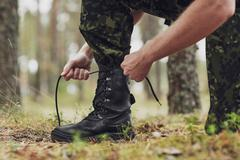 Close up of soldier tying bootlaces in forest Stock Photos