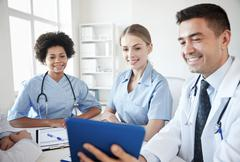 happy doctors with tablet pc meeting at hospital - stock photo